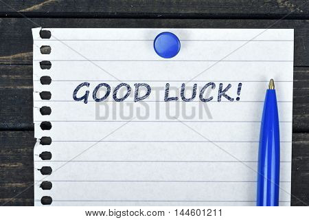 Good Luck text on page and pen on wooden table