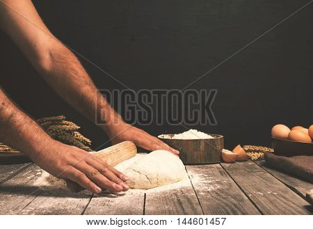 Men hands roll out dough close up. Man preparing dough for cooking pasta on a wooden table