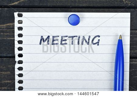 Meeting text on page and pen on wooden table