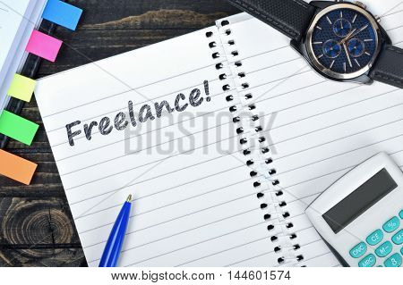 Freelance text on notepad and watch on desk