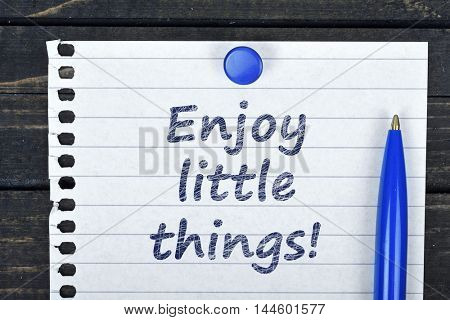 Enjoy little things text on page and pen on wooden table