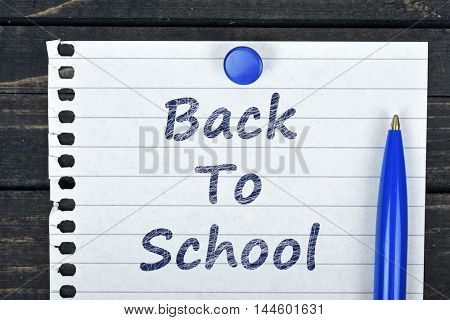Back to school text on page and pen on wooden table