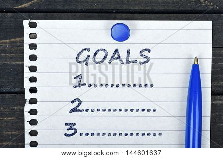 Goals text on page and pen on wooden table