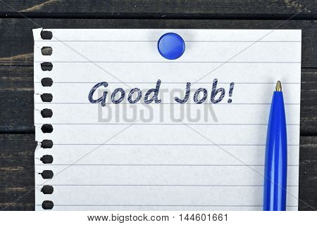 Good Job text on page and pen on wooden table