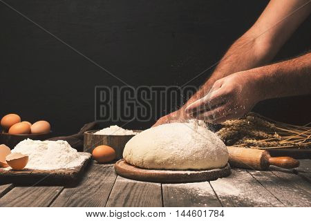 Men hands sprinkle dough flour close up. Man preparing dough for cooking bread on a wooden table