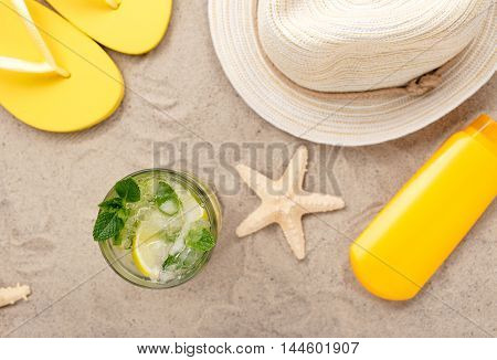 Summer refreshing cocktail on the beach with beach items top view. Focus on the cocktail