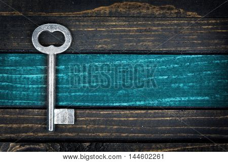 Blue painted line and old key on wooden table