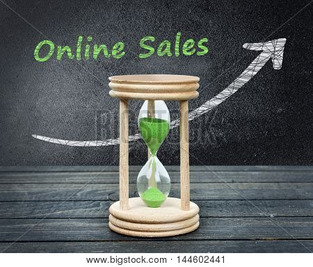 Online sales text and hourglass close-up on wooden table