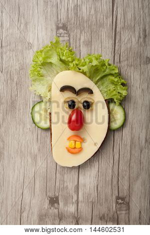 Amusing sandwich face made on wooden background