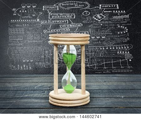 Business plan and hourglass close-up on wooden table