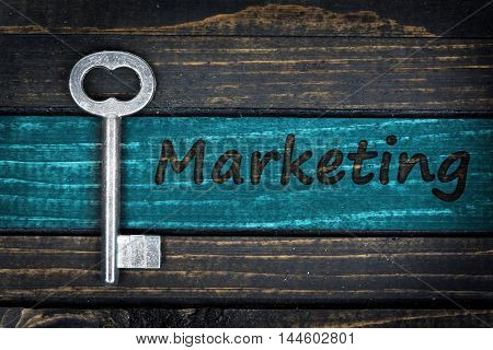 Marketing word and old key on wooden table