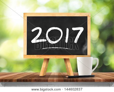 2017 New Year On Blackboard With Coffee Cup,pencil On Plank Wood With Green Abstract Blur Tree Backg