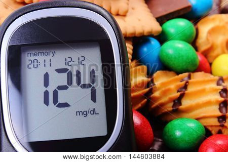 Glucose meter with heap of candies and cookies concept of diabetes and reduction of eating sweets