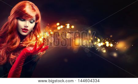Beauty Glamour Woman with golden sparks magic in her hand. Long red wavy hair. Fashion Lady with Beautiful Luxury Hairstyle, makeup, accessories. Isolated on black. Retro Red Silk Gloves, dark dress