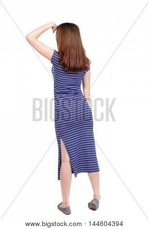 back view of standing young beautiful woman. brunette in a blue striped dress his hand to his eyes looking to the side.