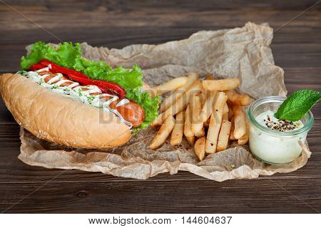 Big tasty hot dog with sausage and vegetables with sauce and French fries on the parchment on the wooden background. hot dogs to gourmet.