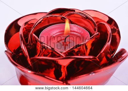 Red candle in candlestick on white background