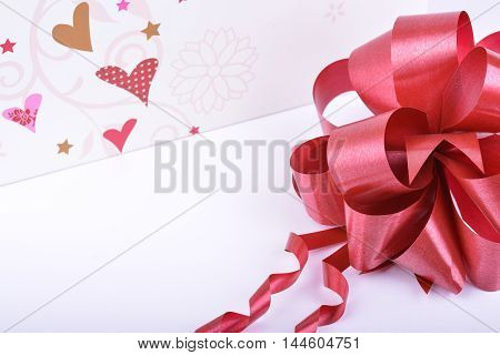Red ribbon bow and hearts on white valentines day concept
