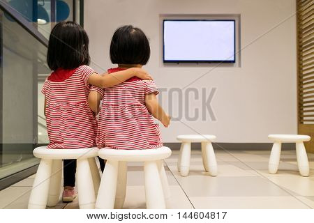 Two Asian Chinese Little Sister Watching TV indoor.