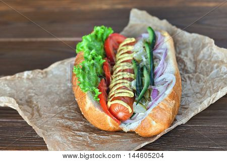 Big tasty hot dog with sausage, vegetables isousom on parchment on the wooden background. hot dogs to gourmet.