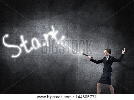 Young elegant businesswoman with flashlight draw word start
