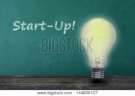 Start-up text on green board and light bulb on table