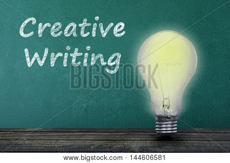 Creative Writing text on green board and light bulb on table
