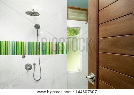 Open wooden door with white shower in bathroom interior