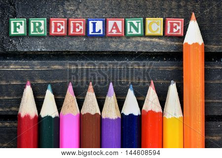 Freelance text and group of pencil on wooden table