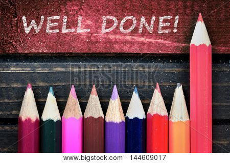 Well Done text and group of pencil on wooden table