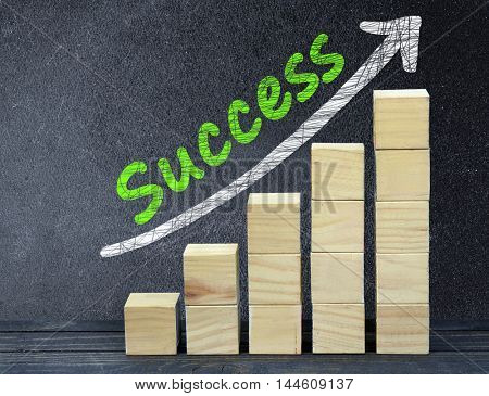 Success text on black board and block stairs