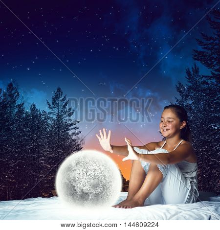 Cute girl in bed looking at glowing moon planet. Elements of this image are furnished by NASA