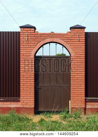 Forged metal gate in the fence with brick pillars with arch