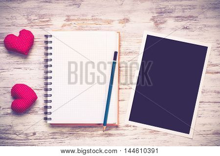 Blank photo frame and notepad on wooden table