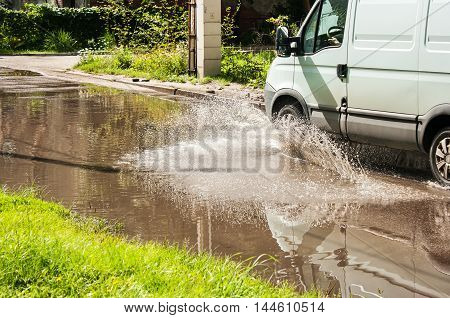 white commercial vehicle riding on big puddle on the road in residental area on sunny summer day closeup