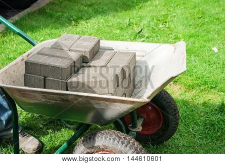 pile of grey paving slabs lying in a wheelbarrow closeup