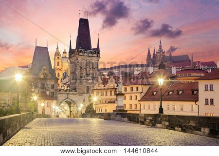View of the Lesser Bridge Tower of Charles Bridge in Prague (Karluv Most) at sunrise, Czech Republic, Europe. This bridge is the oldest in the city and a very popular tourist attraction.
