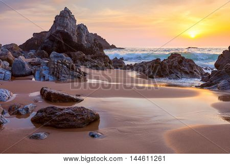 Fantastic big rocks and stones on the ocean beach at golden sundown landscape