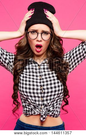 Fashion studio portrait of pretty young hipster brunette woman with glasses , wearing stylish urban t shirt and hat, over pink background.