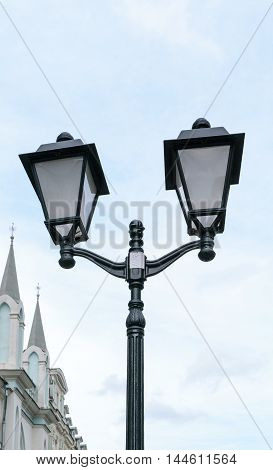 Black retro street lamp with two lights in the sky background