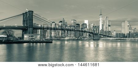 Panoramic view of  Brooklyn Bridge and Manhattan skyline in New York City at morning with city illumination, USA. Black and white toned