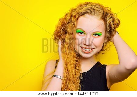 Pretty teen girl with bright make-up posing over yellow background.
