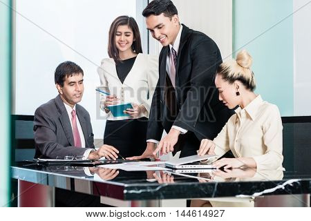Asian business people in meeting room, listening to presentation and looking at charts
