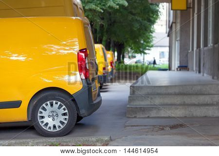 Side view of yellow delivery vans on parking in front on the entrance a warehouse at distribution center. Shallow depth of field.