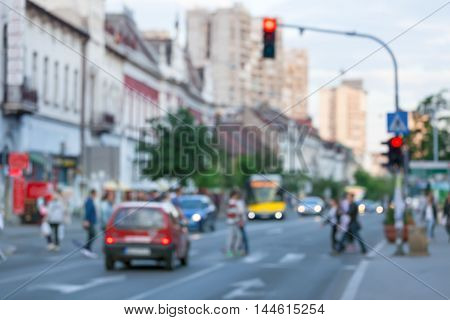 Busy city street with people and cars in motion blur on crosswalk. Traffic lights regulation.