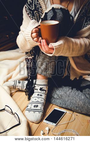 Girl with a cup of coffee sitting on a wooden floor.