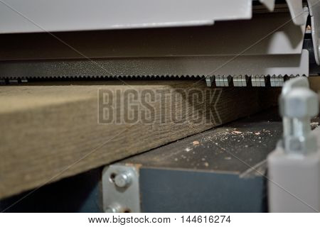 thick wooden board is treated with a planer