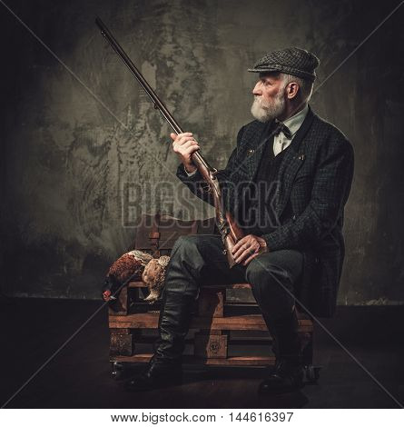 Senior hunter with a shotgun in a traditional shooting clothing, sitting on a dark background.