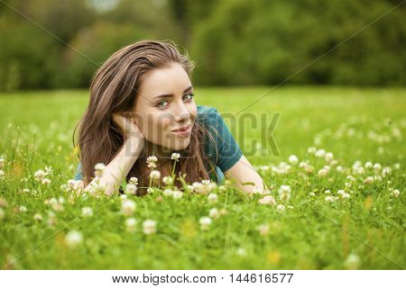 Gorgeous young pretty brunette woman relaxing in summer park