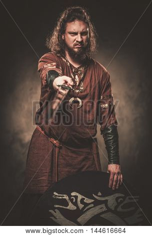 Serious viking with sword in a traditional warrior clothes, posing on a dark background.
